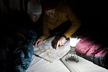 Couple in sleeping bags, looking at trail map, Yak Kharka, Nepal