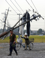 Residents walk next to fallen power poles damaged by what seemed to be a tornado in Koshigaya