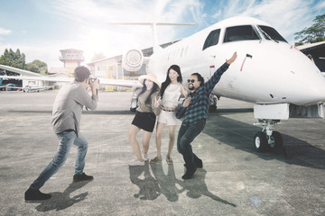 Asian man with his friends near an aircraft