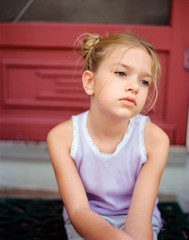 Young girl sitting outside, looking away