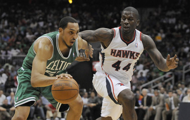 Boston Celtics center Hollins drives past Atlanta Hawks forward Johnson in the second half of their NBA basketball game in Atlanta