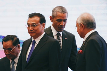 U.S. President Barack Obama walks behind China's Premier Li Keqiang as they attend a family photo at the ASEAN Summit in Kuala Lumpur