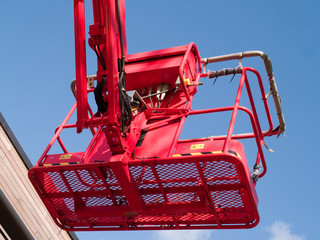 Red cherry picker machine in raised position, seen from below.