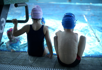 Ismail Zulfic (R), 6-year old armless swimmer sits by the pool in Olympic Pool Otoka in Sarajevo