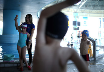 Ismail Zulfic, 6-year old armless swimmer warms up before swimming in Olympic Pool Otoka in Sarajevo
