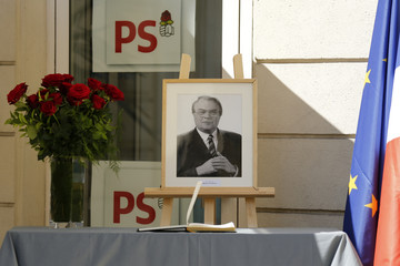 A portrait of former French prime minister Mauroy and a vase of red roses flowers are displayed at the rue de Solferino Socialist Party headquarters in Paris
