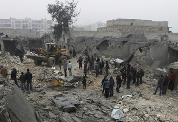 Civilians gather as they inspect a site hit by what activists said was shelling by forces loyal to Syrian President Bashar al-Assad, in the Jazmati area in Aleppo