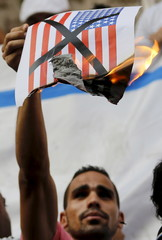 An activist shouts slogans against the U.S. as he burns a picture of their flag during a protest in front of the Syndicate of Journalists in Cairo