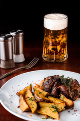 Pork knuckle with potatoes, cabbage and beer on a wooden table. Black background.