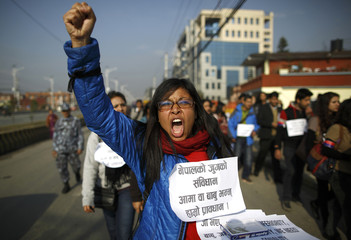 An activist shouts slogans as she holds a banner during a demonstration demanding for the right of Nepali mothers to pass on their citizenship to their children in Nepal