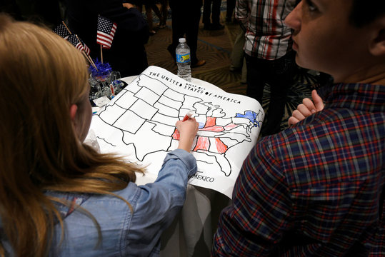A girls colors an electoral map of the United States in either red or blue as returns are announced for the U.S. general election at Republican Governor Pat McCrory's election-night party in Raleigh, North Carolina, U.S.
