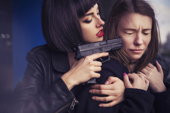 Beautiful brunette sexy spy agent (killer or police) woman in leather jacket and jeans with a gun in her hand catch a girl on parking
