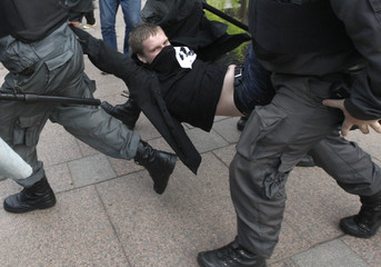 Russian policemen detain an opposition party supporter during a protest rally in central St. Petersburg