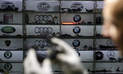 A worker prepares a car light in front of shelves with product samples at Bekto Precisa factory in Gorazde