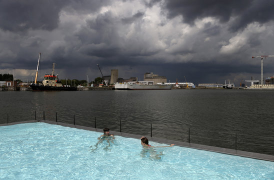 "Two women enjoy a floating open-air swimming pool called ""badboot"" in the port of Antwerp"