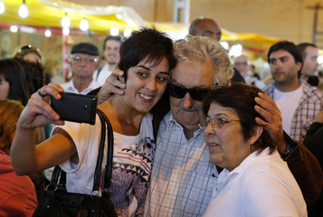 Uruguayan President Jose Mujica takes a picture with women while attending the annual celebrations of Criolla Week in Montevideo