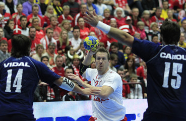 Denmark's Nielsen tries to score next to Argentina's Vidal and Carou in their main round match at the Men's Handball World Championship in Malmo