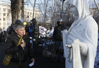 Anti-government protesters pray at a religious statue in Kiev