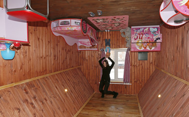 A visitor poses for a picture in a room of a house built upside-down in Russia's Siberian city of Krasnoyarsk