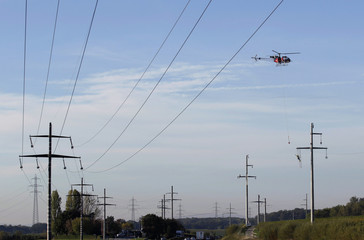 An helicopter hovers as workers install an electrical power line for Romande Energie near Nyon