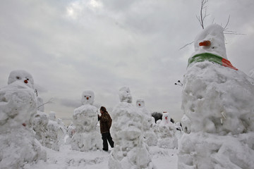 A woman walks amidst snowmen at Gorky city park in Moscow
