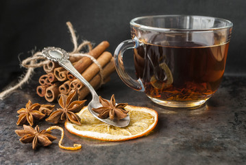 Anise and cinnamon sticks with a cup of tea on a dark background