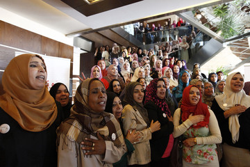 Women candidates sing the national anthem before taking a group photo at a conference to empower women voters and politicians in Tripoli