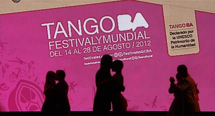 Couples are silhouetted in front of screen during Salon style Tango World Championship qualifiers in Buenos Aires