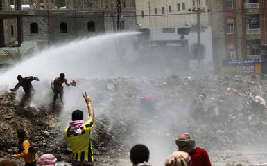 Police use water cannons to disperse anti-government protesters during a demonstration demanding the ouster of Yemen's President Saleh in the southern city of Taiz