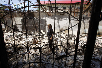 An ethnic Uzbek woman stands amid the debris of her family house burnt down during ethnic clashes in the southern Kyrgyz city of Jalalabad