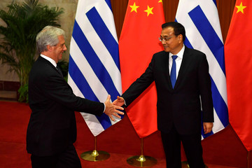 Uruguay's President Tabare Vazquez shakes hands with Chinese Premier Li Keqiang before their meeting at the Great Hall of the People in Beijing