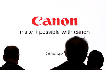 People are silhouetted against a display of the Canon brand logo at the CP+ camera and photo trade fair in Yokohama