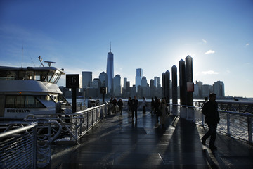 New York skyline and the One World Trade Center are seen in the distance as people make their commute after a night of snow from  Exchange Place in New Jersey to New York City