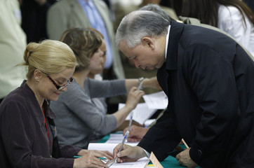 Presidential candidate of Poland's Law and Justice Party Kaczynski signs ballot papers at polling station in Warsaw during presidential elections