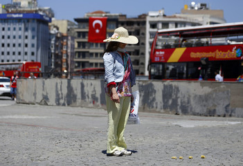 A woman stands during a silent protest at Taksim Square in Istanbul