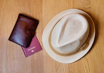 Travel accessories. Hat, wallet, passport on wooden background