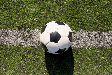 soccer ball on football field marking line