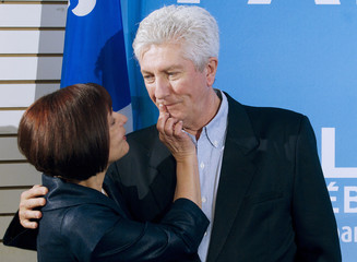 Bloc Quebecois leader Gilles Duceppe has lipstick wiped off his lips following a kiss from his wife during a campaign stop in Montreal