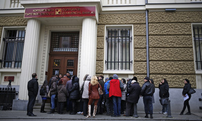 Customers wait to clarify details on their deposits outside the main office of Bulgaria's Corpbank in Sofia