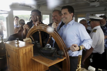 Wisconsin Governor Scott Walker poses with former governors Jim Gilmore of Virginia and Bob Erlich of Maryland for a photo during a sunset cruise with the Belknap County Republicans in Laconia