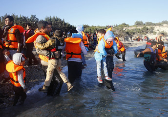 Refugees carrying their children walk towards a dinghy to sail off for the Greek island of Chios from the western Turkish coastal town of Cesme