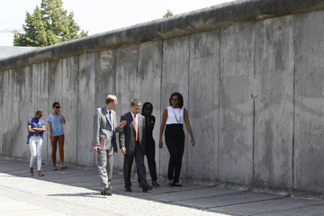US first lady Michelle Obamavisits the Berlin Wall memorial Bernauer Strasse with her husband's half sister Auma Obama her daughters Sasha and Malia and Joachim Sauer in Berlin