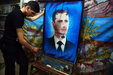 A youth plays with a game made from remnants of mortar shells and decorated with a defaced picture of Syria's President Bashar al-Assad at a basement in the Duma neighbourhood in Damascus