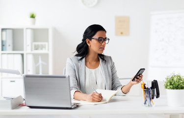 businesswoman with smartphone and laptop at office
