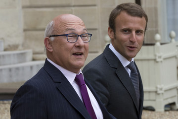 French Finance minister Sapin and newly-named Economy minister Macron leave the Elysee Palace following the weekly cabinet meeting after a government reshuffle in Paris