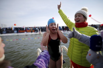 A female swimmer reacts after finishing the competition in a pool carved from thick ice covering the Songhua River during the Harbin Ice Swimming Competition in the northern city of Harbin