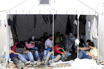 Group of migrants wait in a shelter as it rains at a transit camp near Gevgelija, Macedonia, after entering the country by crossing the border with Greece