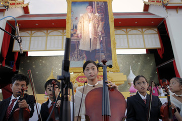 Children hold their musical instruments under a picture of Thailand's King Bhumibol Adulyadej as people gather outside the Royal Palace in Bangkok