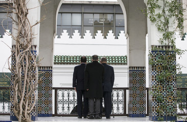 Paris Mosque rector Boubakeur and French President Hollande stand to attention during national anthems, after a ceremony at the Grand Mosque of Paris