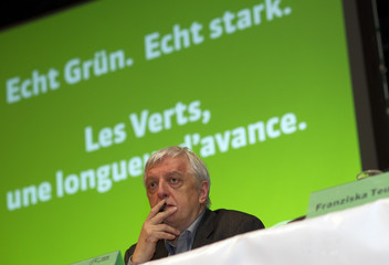 "Swiss Green Party President Ueli Leuenberger sits in front of a background that says ""real green. real strong."" during a party meeting Kriens"